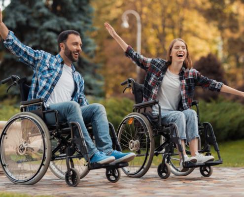 man woman wheelchairs ride around park